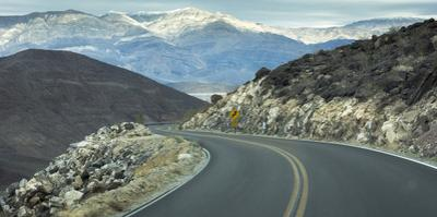 Road with Curve Leading Through Mountains into Death Valley, California by Sheila Haddad