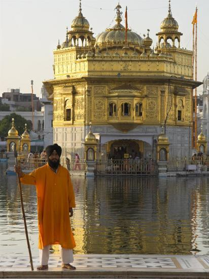 Shrine Guard in Orange Clothes Holding Lance Standing by Pool in Front of the Golden Temple-Eitan Simanor-Photographic Print