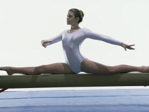 Side Profile of a Female Gymnast Stretching on a Balance Beam