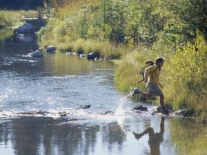 Side Profile of a View of a Young Man Running Across a River