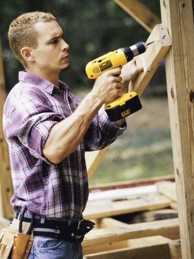 Side Profile of a Young Man Using an Electric Drill--Photographic Print