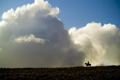 Silhouette of a Cowboy Riding across a Ridge with a Cumulonimbus Cloud in the Background-Jonathan Kingston-Photographic Print