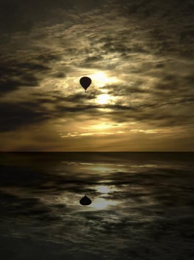 Silhouette of a Hot Air Balloon Over Water--Photographic Print