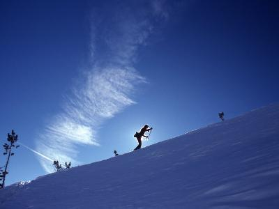 Silhouette of a Woman Cross Country Skiing Up a Snowy Slope, Mount Rose, Nevada, United States-Kate Thompson-Photographic Print
