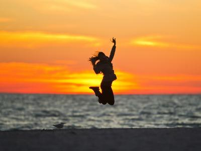 Silhouette of a Woman Jumping in Front of a Colorful Beach Sunset-Mike Theiss-Photographic Print