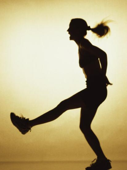 Silhouette of a Young Woman Exercising--Photographic Print