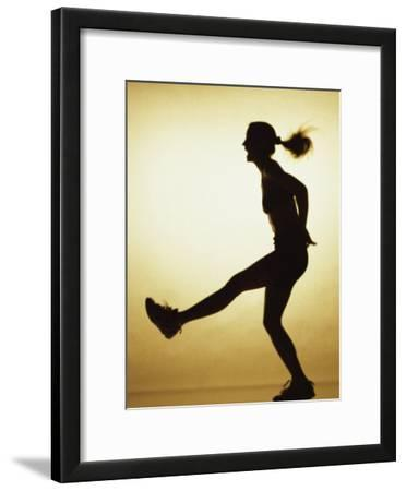 Silhouette of a Young Woman Exercising