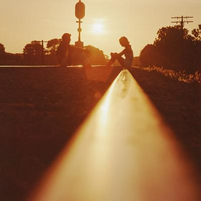 Silhouette of Couple Sitting on Railroad Tracks at Sunset-Dennis Hallinan-Photographic Print