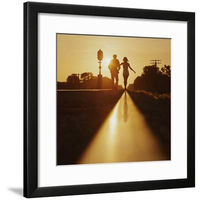 Silhouette of Couple Walking on Railroad Tracks at Sunset-Dennis Hallinan-Framed Photographic Print