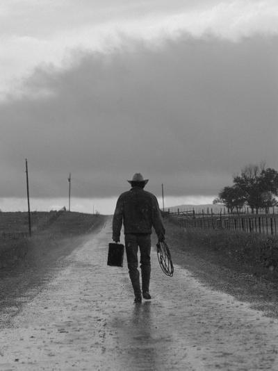 Silhouette of Cowboy Walking on Empty Road--Photographic Print
