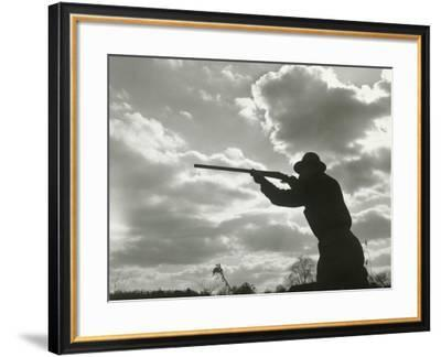 Silhouette of Man Aiming Shotgun Outdoors--Framed Photographic Print