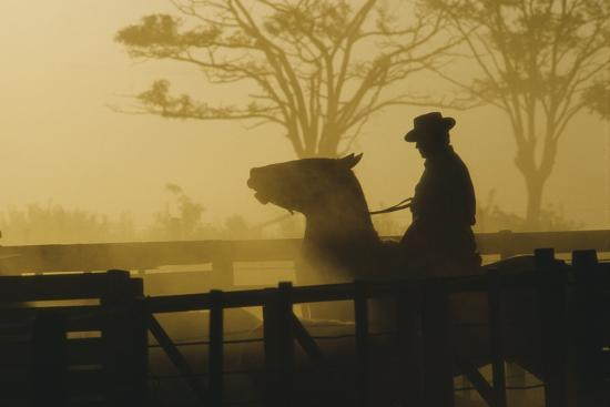 Silhouette of Man Riding Horse at Dusk-Nicolas Russell-Photographic Print