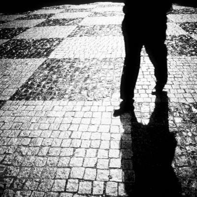 Silhouette of Mans Legs Walking on Cobblestone Street at Night-Elke Hesser-Photographic Print