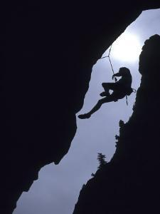Silhouette of Rock Climber Hanging from Cliff Face