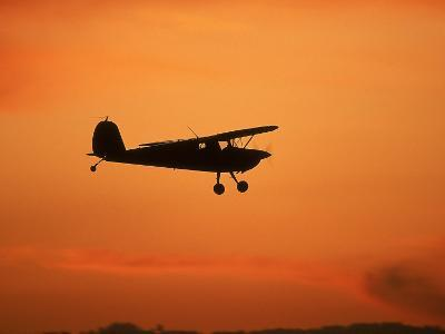 Silhouette of Small Airplane in Flight-Kyle Krause-Photographic Print