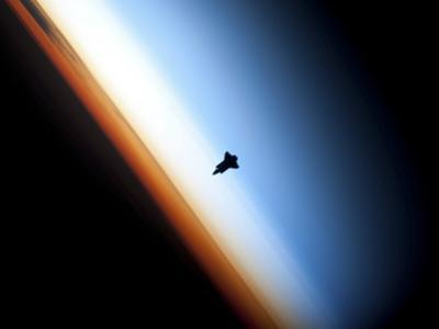 Silhouette of Space Shuttle Endeavour over Earth's Colorful Horizon