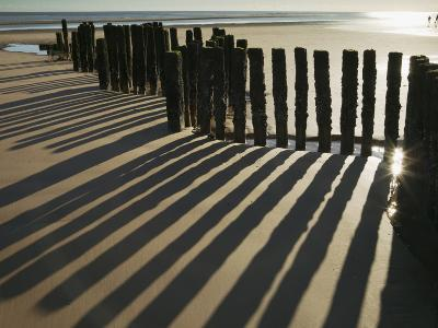 Silhouette of the Remains of a Groyne on the Beach at Dawlish Warren-Nigel Hicks-Photographic Print