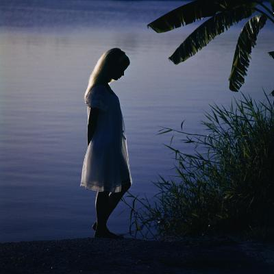 Silhouette of woman standing near a lake-Dennis Hallinan-Photographic Print