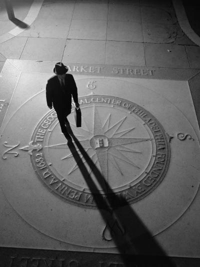 Silhouetted Businessman With Briefcase Walking Across Compass in the Sidewalk-H^ Armstrong Roberts-Photographic Print