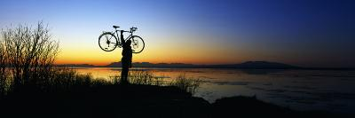 Silhouetted Cyclist Holding Bicycle over Head, River's Edge, Sunset, Alaska--Photographic Print