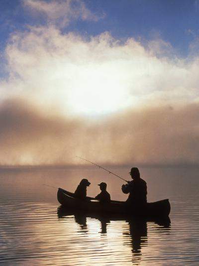 Silhouetted Father and Son Fishing from a Canoe-Bob Winsett-Photographic Print