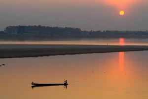 Silhouetted Man in Longtail Boat Along the Mekong River