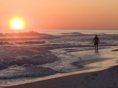 Silhouetted Man Walking Along the Beach at Sunset-Marc Moritsch-Photographic Print