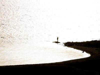 Silhouetted Person on a Point of Land Jutting Out into Calm Water-Mattias Klum-Photographic Print