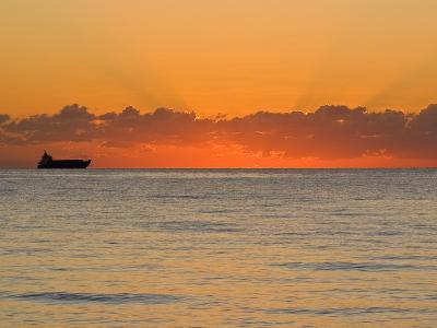 Silhouetted Ship Moments before the Sun Rises over the Horizon-Mike Theiss-Photographic Print