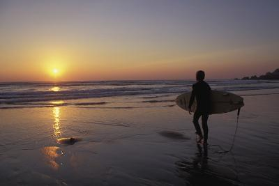 Silhouetted Surfer on Sandy Beach at Sunset-Design Pics Inc-Photographic Print