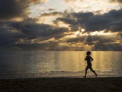 Silhouetted Woman Jogging on a Beach at Twilight-Mattias Klum-Photographic Print