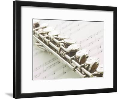 Silver Flute on Sheet of Music