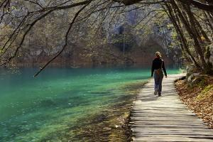 Visitor on Wooden Walkway Path over Crystal Clear Waters of Plitvice Lakes National Park by Simon Montgomery