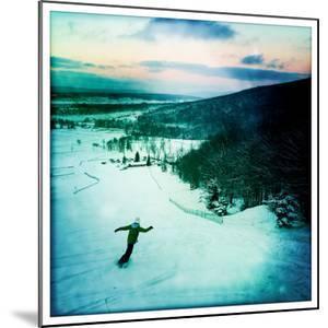 A Boy Snowboards Downhill Through Powder by Skip Brown