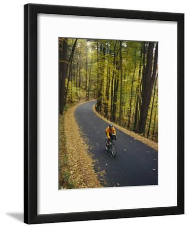 A Cyclist Riding Along a Rural Road in the Fall