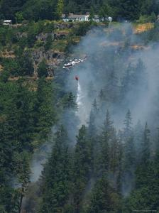 A Firefighting Helicopter Douses a Forest Fire Threatening Homes by Skip Brown