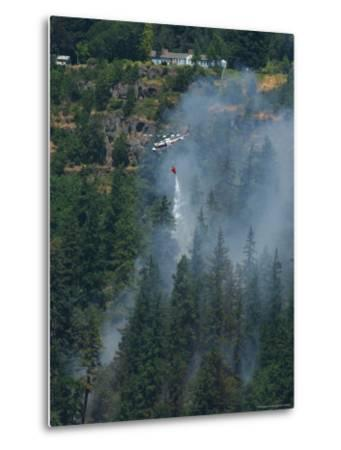 A Firefighting Helicopter Douses a Forest Fire Threatening Homes
