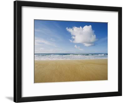 A Large Cloud Dominates the Sky as the Surf Rolls onto a Sandy Beach