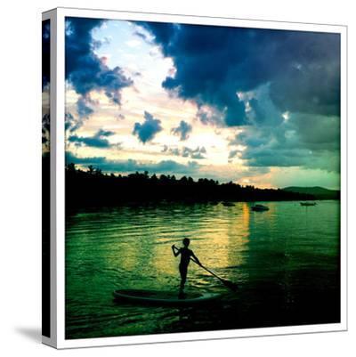 A Seven Year Old Girl Paddles a Paddle Board at Sunset on Sebago Lake