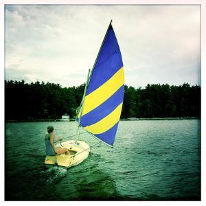 A Woman Sails a Small Boat across Sebago Lake by Skip Brown