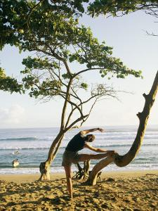 A Woman Stretches Her Body on a Small Tree at a Sandy Beach by Skip Brown