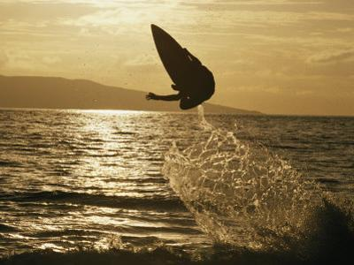 An Airborne Skimboarder is Silhouetted at Twilight