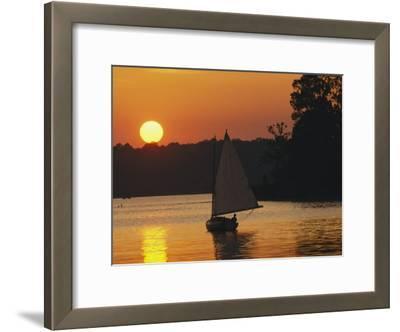 Gaff-Rigged Catboat Sails Along the Shoreline at Sunset