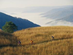 Mountain Bikers on Trail Above Fog-Covered Elk River Valley by Skip Brown