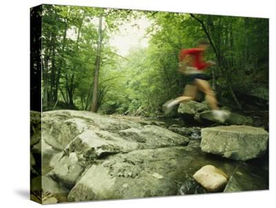 Panned View of Man Leaping over Rocky Stream on the Appalachian Trail