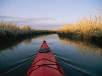 The Bow of a Kayak Leads the Way Through a Marsh Channel