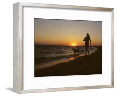 Woman and Her Dog Running Along Currituck Sound Beach at Sunset, Nags Head, North Carolina