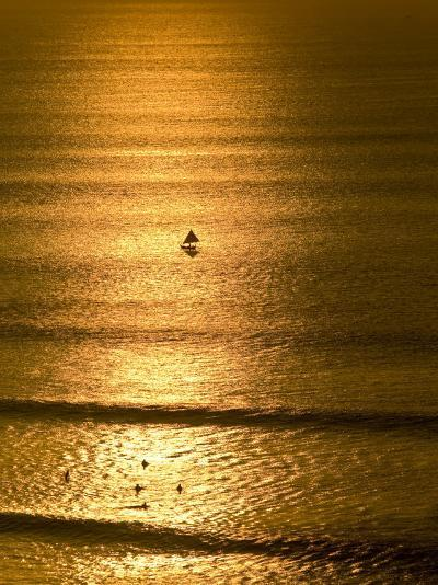 Small Fishing Boat Heads Out to Sea at Sunset Past Surfers-Jason Edwards-Photographic Print