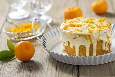 Small Orange Cake with White Icing on Wooden Table-Jana Ihle-Photographic Print