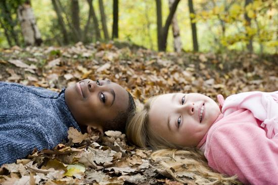 Smiling Children Lying on Autumn Leaves-Ian Boddy-Photographic Print